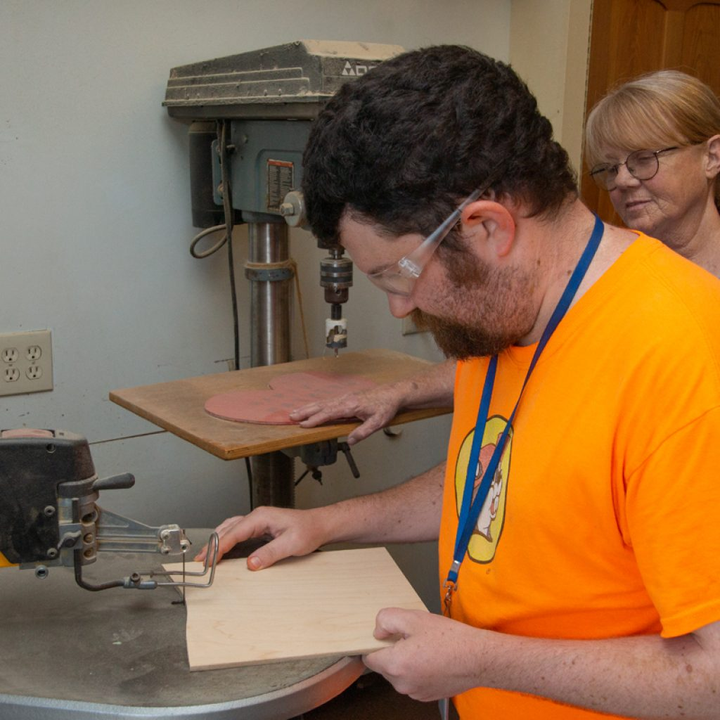 Adult with disabilities learns how to use scroll saw